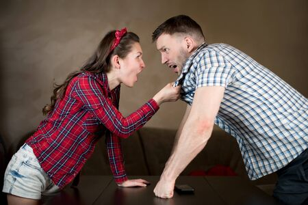 Photo pour The wife scolds her husband and pats him on the shirt. Family showdown, scolding, crisis in family relationships - image libre de droit