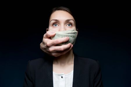 Photo pour Corruption and bribery cover the woman s mouth with money. Business woman looking into the void, dollars are pressed to her mouth by hand from the dark - image libre de droit