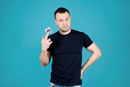 Photo pour Athletic young man with stubble holds a condom in his hand and looks hintingly. Isolated on blue - image libre de droit