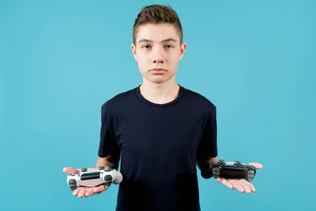Photo pour A teenager in a blue T-shirt with a calm face holds two joysticks in his hands. White and black modified joysticks without identification marks in the guy s hands. Blue background, studio shot - image libre de droit