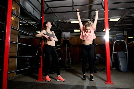 Photo pour girl arrogantly watches another girl try to pull herself up on the horizontal bar in a gym - image libre de droit