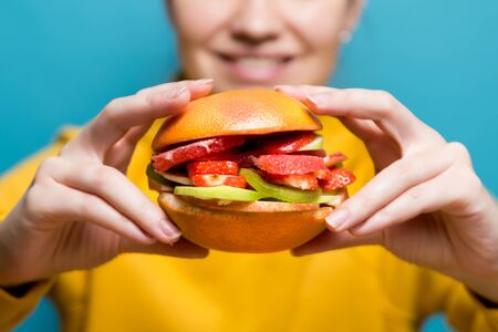 Photo pour young woman holding a vegetarian burger made of fruits and berries, close up - image libre de droit