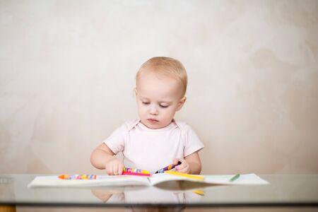 Photo pour little girl chooses a pencil for drawing in an album - image libre de droit