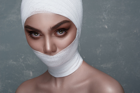 Beauty Girl with big Eyes and white Bandage on her Head and Mouth