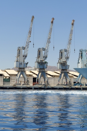 Row of cranes and their reflections in the sea in Eilat harbor, Israel