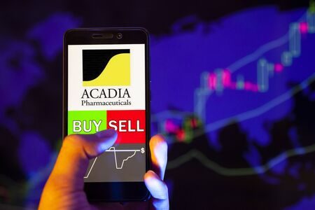 YESSENTUKI, RUSSIA - July 27, 2019: Company logo ACADIA Pharmaceuticals Inc. (ACAD) on smartphone screen, hand of trader holding mobile phone showing BUY or SELL on background of stock chart