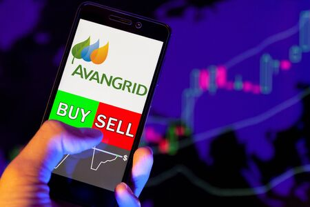 YESSENTUKI, RUSSIA - July 27, 2019: Company logo Avangrid Inc (AGR) on smartphone screen, hand of trader holding mobile phone showing BUY or SELL on background of stock chart