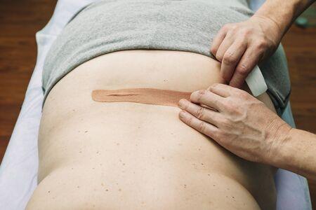 Foto de physical therapist placing kinesio tape on patient s back - Imagen libre de derechos