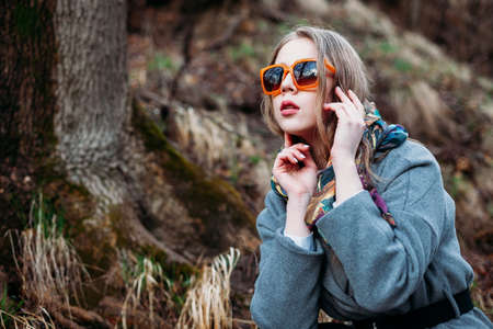 Photo for stylish young woman in orange bright glasses posing in a Park in autumn - Royalty Free Image