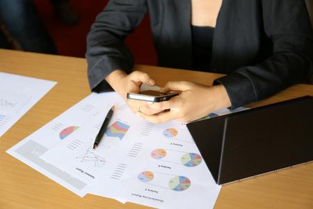 woman in black dress using smart phone on working desk