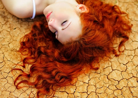 Beautiful young woman with red hair on the dried up ground