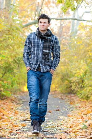 Photo for Young smiling man walking in autumn park. - Royalty Free Image