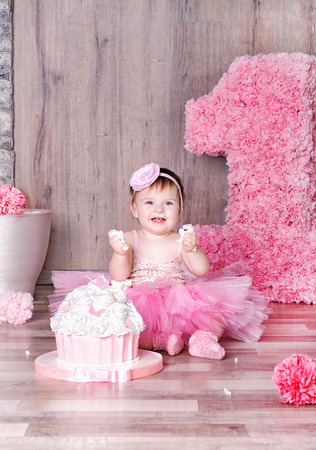 Photo pour Cute smiling baby girl eating first birthday cake, smeared face. - image libre de droit