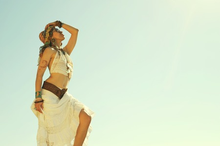 Photo pour Young beautiful boho style woman standing outdoor against sky, vintage bleached colors, hippie, indie style, african outfit - image libre de droit
