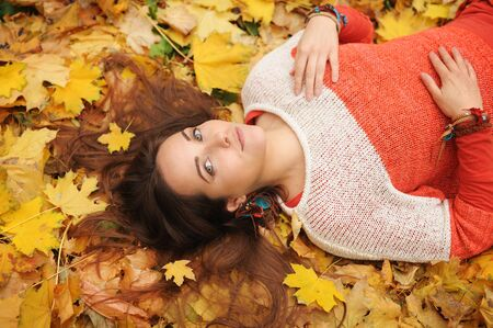 Photo pour Smiling happy womanl portrait, lying in autumn leaves, dressed in fashion sweater, autumn outdoor - image libre de droit