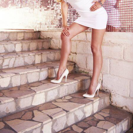 Photo pour Sexy woman legs in luxury white high heel shoes - image libre de droit