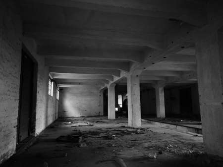 Photo pour Inside an abandoned concrete building, an old messy industrial warehouse with small windows and large doors during the day. - image libre de droit