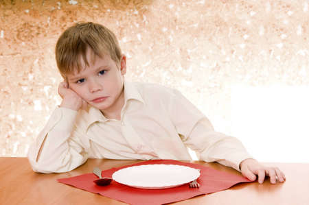 pensive child sits near an empty plate and  looks ahead