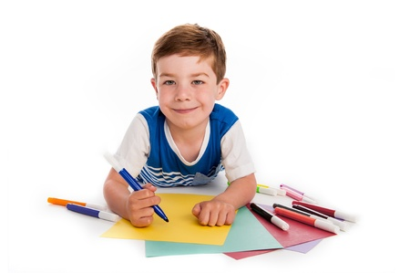 Smiling young boy with felt pens writing and drawing on  colourful paper. White background.