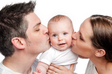 Photo for Young Mother Father Kissing Baby  Studio shot on white background   - Royalty Free Image