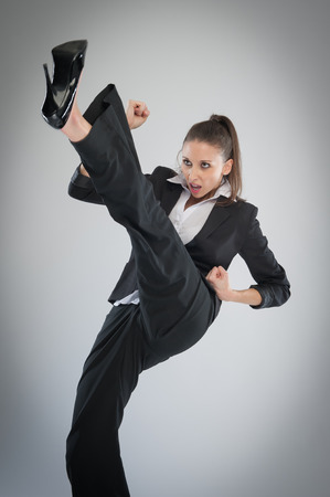 Agressive woman in high heels kicking into the air. Martial Art Karate pose in the studio on grey background.