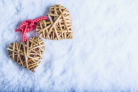 Photo for Two entwined beige flaxen hearts tied together with a ribbon on white snow. - Royalty Free Image