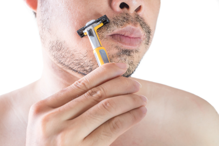Asian young man using a razor shaving his beard. Do not use cream. on white background and clipping path. Clean face treatment concept.