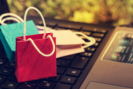 Three colorful paper shopping bags on notebook keyboard. business concept of online shopping. e-commerce or services on the internet is a transaction of buying or selling goods via electronic system