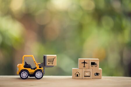 Photo for Logistic network distribution and cargo freight concept: Mini fork-lift truck moves a pallet with wooden block with icon. depicts delivering goods or products around globe in e-Commerce. - Royalty Free Image