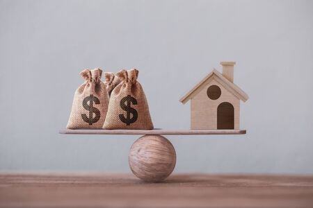 Photo pour US dollar hessian bags with house paper model on a wood balance scale. Home loan, reverse mortgage concept, Depicts a homeowner or a borrower turns properties into cash - image libre de droit