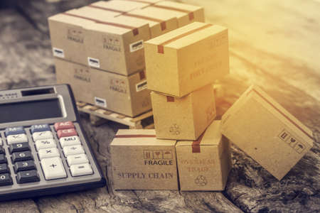 Photo for business concept: Cardboard boxes and calculator. Concept of Increasing product rates the expansion of export business to plan marketing or finance go future. - Royalty Free Image