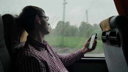 Young man checking emails on his commute to a job by the bus in a long trip. Close-up of using a mobile phone.
