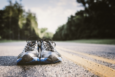 Foto de Lone pair of new running shoes, just waiting to be used on an open road - Imagen libre de derechos