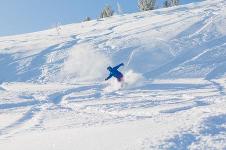 Snowboarder riding fresh snow powder in mountains.