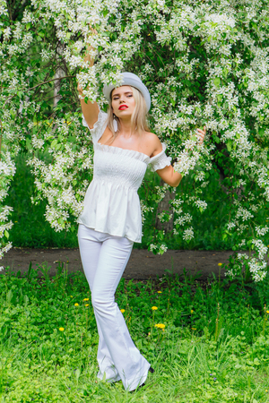 Foto de Sexy modern bride in white cylinder hat enjoing blooming apple tree flowers in spring time - Imagen libre de derechos