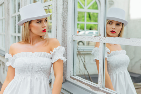 Foto de modern bride in white cylinder hat looks at her reflection in mirror window of an old vintage building - Imagen libre de derechos