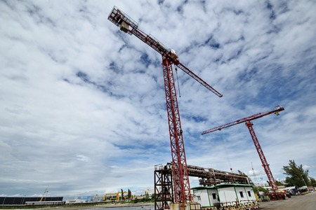 Wide angle view of 2 Large shipyard powercranes are installed on platform for loading used for repaired dock.