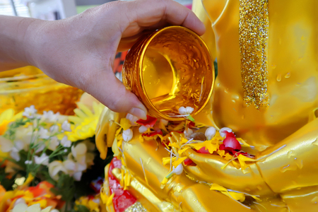 Photo pour Pour some water with refreshing and colorful flower in metallic gold bowl on the hand of golden Buddha image to worship in the Songkran Festival. - image libre de droit