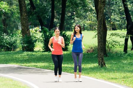 Foto de Couple of girl go exercise in a park and feeling friendly - Imagen libre de derechos