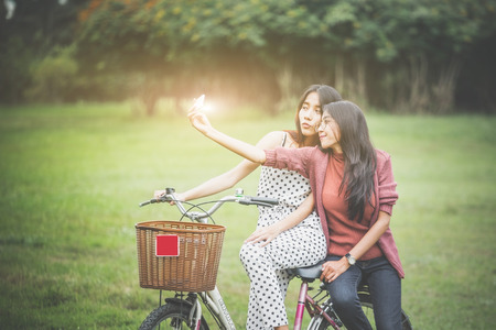 Photo pour Girls ride a bicycle  in park, having fun by play together - image libre de droit