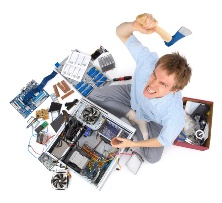 Stressed man with ferocious expression decides to solve his computer problems with an axe