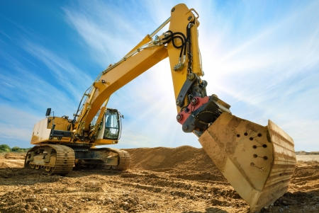 Photo pour Big excavator on new construction site, in the background the blue sky and sun - image libre de droit
