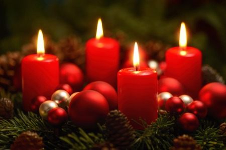 Low-key studio shot of a nice advent wreath with baubles and four burning red candles