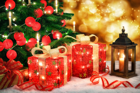 Shiny Christmas scene with a Christmas tree and illuminated red baubles, ornamental gift boxes with lamps, a lantern and bokeh lights background