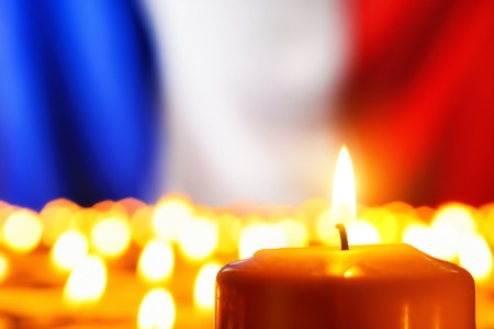 Lots of candles in front of the national colors of France in remembrance of the many victims of terror or to simply symbolize the great French spirit