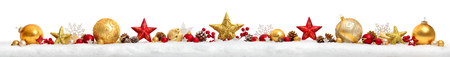 Foto de Christmas border or banner with stars and baubles arranged in a row on snow, extra wide and isolated on white background - Imagen libre de derechos