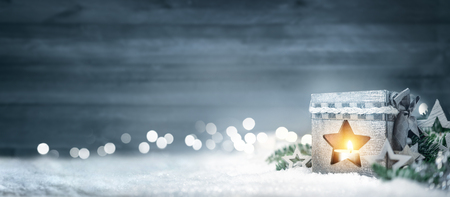 Foto per Christmas background in cool winter colors with a shining lantern, wood board, fir branches, ornaments and out of focus lights - Immagine Royalty Free