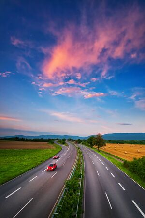 Photo pour Wide, almost empty road under the colorful sky after sunset, with beautiful red clouds and two red cars with slight motion blur, a dynamic transportation and landscape shot - image libre de droit