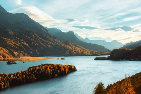 Epic view on autumn lake Sils (Silsersee) in Swiss Alps. Autumn forest with yellow larch on background. Landscape photography