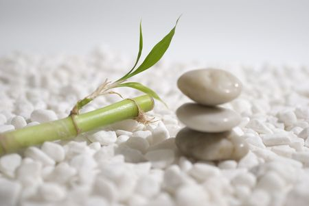 zen stones and bamboo on white pebbles background - meditation concept